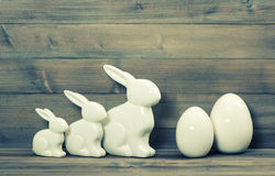 Easter bunny family and white ceramic eggs. Vintage easter decor Royalty Free Stock Photos