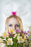 Easter bunny female looking over flowers Royalty Free Stock Photos