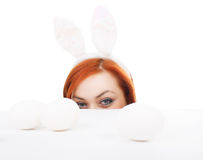 Easter bunny female looking over table for easter eggs Royalty Free Stock Images