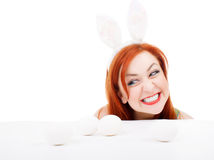 Easter bunny female looking over table for easter eggs Stock Photos