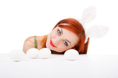 Easter bunny female looking over table for easter eggs Royalty Free Stock Photo