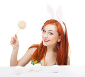 Easter bunny female looking over table for easter eggs Royalty Free Stock Photography