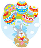 Easter Bunny flies with balloons. Little rabbit flies in a basket with balloons colored like Easter eggs Stock Photos