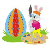 Easter Bunny 006. Funny cute Easter Bunny with a brush and palette coloring big egg by fantastic colors Stock Images