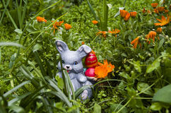 Easter bunny in the garden. Easter bunny is bringing colored eggs in his basket Stock Images