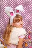 Easter bunny girl with funny ears. On purple background with dots Stock Photo