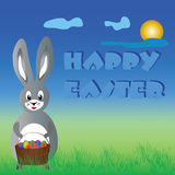 Easter bunny. On grass with a basket of eggs Stock Photography