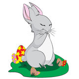 Easter bunny in the grass. Easter rabbit on a green lawn Royalty Free Illustration