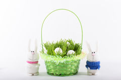 Easter bunny with a green basket and white eggs Royalty Free Stock Photo