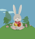 Easter bunny 18. On the green lawn Easter bunny sits and holds in paws painted Easter eggs. Vector illustration Stock Photography