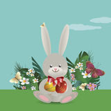 Easter bunny 2. On the green lawn Easter bunny sits and holds in paws painted Easter eggs. Vector illustration Stock Photo