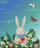 Easter bunny 1. On the green lawn Easter bunny sits and holds in paws painted Easter eggs. Vector illustration Royalty Free Stock Image