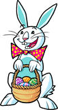 Easter bunny holding a basket. White easter bunny holding a basket filled with decorated eggs Stock Images