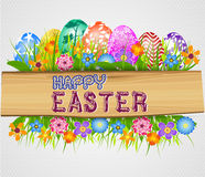 The Easter bunny holding a basket of Easter eggs with more Easter eggs  and wood sign board Stock Photography