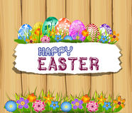 The Easter bunny holding a basket of Easter eggs with more Easter eggs  and wood sign board Royalty Free Stock Image