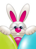 Easter bunny holding colorful eggs over white background Royalty Free Stock Images