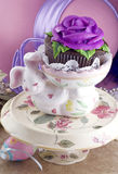 Easter Bunny Holding Cupcake. A ceramic Easter bunny holding a beautifully decorated cupcake with a purple rose, on a pretty spring cake stand, vertical with Stock Images