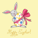 Easter bunny is holding egg in paws stock images