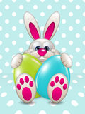 Easter bunny holding eggs over light blue Royalty Free Stock Images