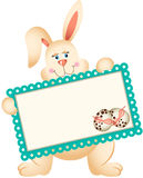Easter Bunny holding greeting card Stock Photo