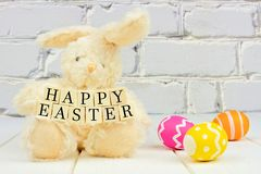 Easter bunny holding Happy Easter wooden blocks Stock Photos