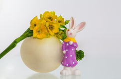 Easter bunny ith egg and flower. A bunny standing in front of an egg with flowers Royalty Free Stock Photography
