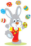 Easter Bunny juggler. Little rabbit juggling with colorful Easter eggs Royalty Free Stock Photos