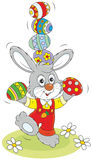 Easter Bunny juggler. Little rabbit juggling with colorful Easter eggs Stock Photos