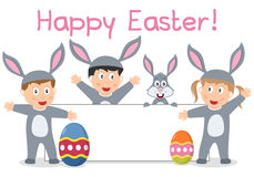 Easter Bunny Kids and Banner. A group of four cute kids dressed as bunnies with Easter eggs and a blank banner. Empty space for your message. Eps file available Royalty Free Stock Photography