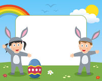 Easter Bunny Kids Photo Frame. Photo frame, post card or page for your scrapbook. Subject: two happy kids dressed as bunnies with Easter egg in a park with Stock Photos