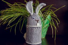 The Easter Bunny is knitted souvenir on the occasion. Handmade easter bunny with colorful flowers and easter eggs Royalty Free Stock Photography
