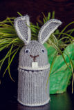 The Easter Bunny is knitted souvenir on the occasion. Handmade easter bunny with colorful flowers and easter eggs Stock Photo