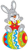 Easter Bunny. Little rabbit sitting on a big decorated Easter egg Stock Photo