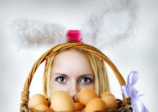 Easter bunny looking over eggs basket Royalty Free Stock Photo