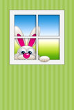 Easter bunny looking by the window. With place for text Royalty Free Stock Photo