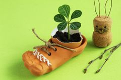 Fragile tender sprout in eggshell in brown ceramic shoe with jute cord, homemade Easter bunny from cork and paper clips and birch stock photo