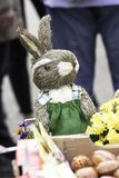 Easter Bunny with flowers and Easter Eggs. Easter Bunny made out of straw, surrounded by decorated easter eggs and spring flowers, wearing a green dress with Royalty Free Stock Images