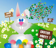 Easter bunny in a meadow with colorful eggs Stock Photo