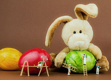 Easter bunny. Miniature painters painting easter eggs Stock Photography