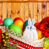Easter bunny with multicolored eggs. On wooden background stock image