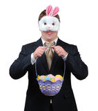 Easter Bunny Outfit 1. Young man wearing suit with Easter Bunny mask, holding an Easter basket full of brightly coloured eggs royalty free stock photos