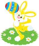 Easter Bunny and painted egg. Vector clip-art of Easter Bunny holding a colorful painted egg overhead Stock Image