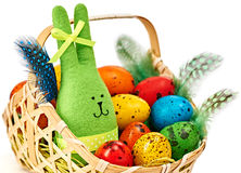 Easter Bunny and painted Eggs in basket on white background Stock Photos