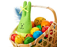 Easter Bunny and painted Eggs in basket on white background Stock Photo