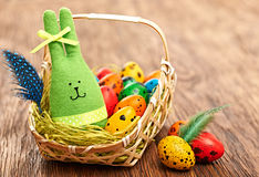 Easter Bunny and painted Eggs in basket on wooden background Stock Photos