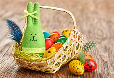 Easter Bunny and painted Eggs in basket on wooden background Royalty Free Stock Image