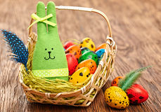 Easter Bunny and painted Eggs in basket on wooden background Royalty Free Stock Photos
