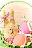 Easter Bunny and painted Eggs in basket on wooden. Easter Bunny Handmade and painted Eggs in decorated green basket with straw on wooden background Stock Photo