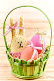 Easter Bunny and painted Eggs in basket on wooden. Easter Bunny Handmade and painted Eggs in decorated green basket with straw on wooden background Royalty Free Stock Photography