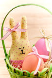 Easter Bunny and painted Eggs in basket on wooden. Easter Bunny Handmade and painted Eggs in decorated green basket with straw on wooden background Stock Image